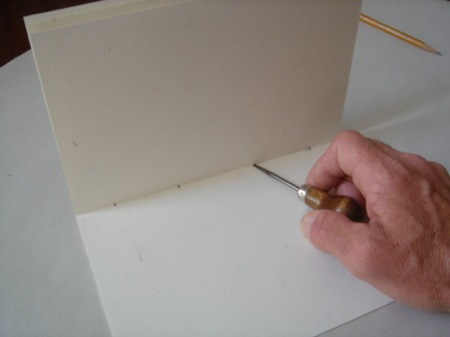 Punching holes in folded signature.