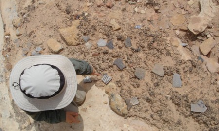 Nicolai studies potsherds on the edge of a midden.